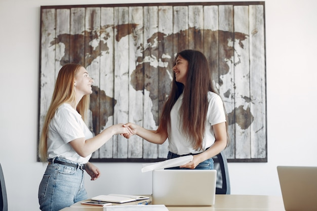 Dos chicas con una camiseta blanca trabajando en la oficina