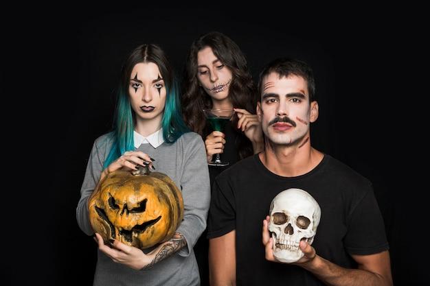 Dos chicas y chico con decoraciones de halloween