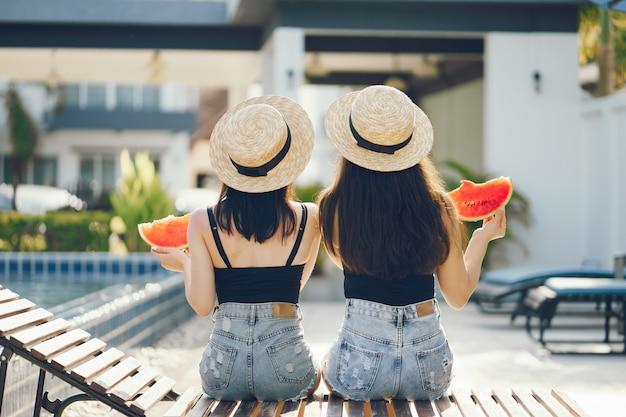 Dos chicas comiendo sandía junto a la piscina en tailandia