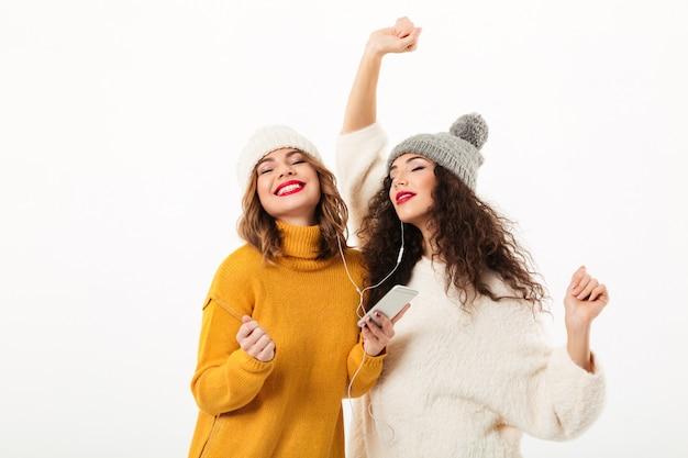 Dos chicas complacidas con suéteres y sombreros bailando juntas sobre una pared blanca