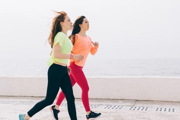 Dos chicas delgadas en ropa deportiva corriendo en la playa por la mañana