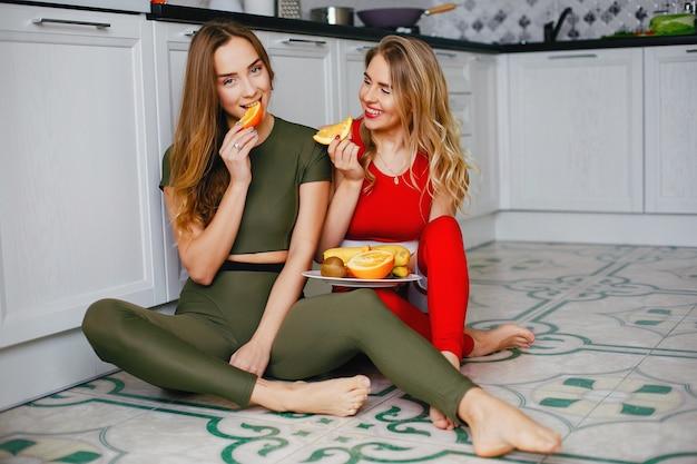 Dos chicas deportistas en una cocina con verduras.