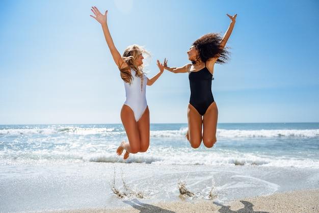 Dos chicas divertidas con hermosos cuerpos en traje de baño saltando en una playa tropical.