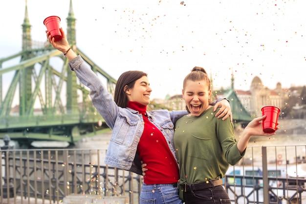 Dos chicas divirtiéndose en una fiesta en una terraza