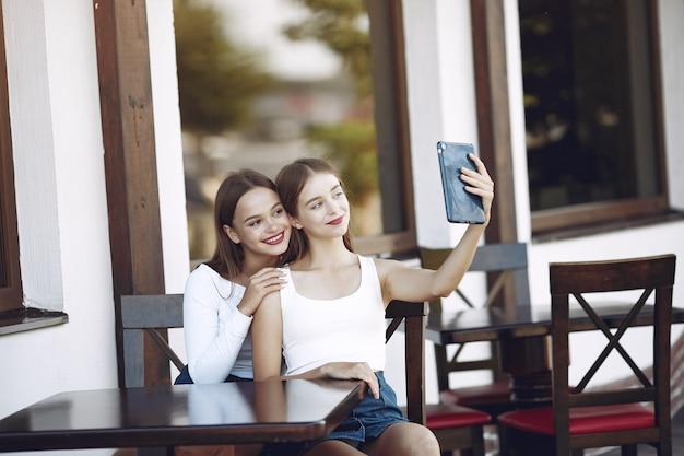 Dos chicas elegantes y con estilo en un café de verano.