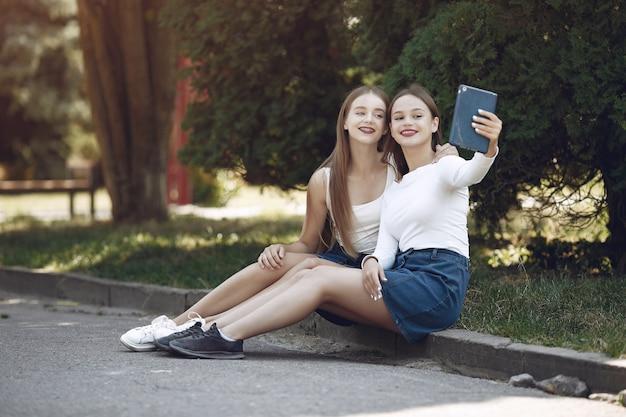 Dos chicas elegantes y con estilo en un parque de primavera