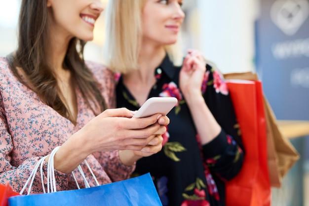 Dos chicas eligiendo la siguiente dirección de compras.