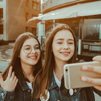 Dos chicas felices mejores amigas transmitiendo video en vivo en la calle de la ciudad