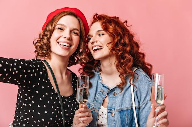 Dos chicas glamorosas sosteniendo copas de vino y tomando selfie. señoras alegres disfrutando de champán y expresando emociones positivas.