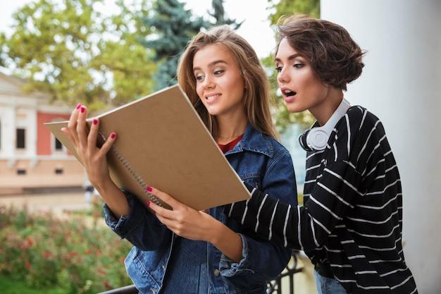 Dos chicas guapas adolescentes jóvenes estudiando juntos