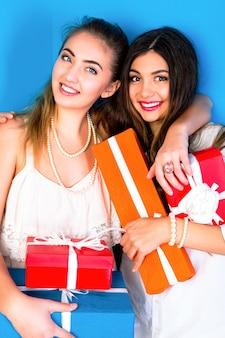 Dos chicas guapas amigas sosteniendo brillantes regalos navideños