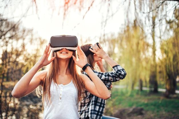 Dos chicas guapas disfrutan de gafas de realidad virtual al aire libre.