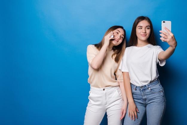Dos chicas guapas están haciendo selfie sobre pared azul.