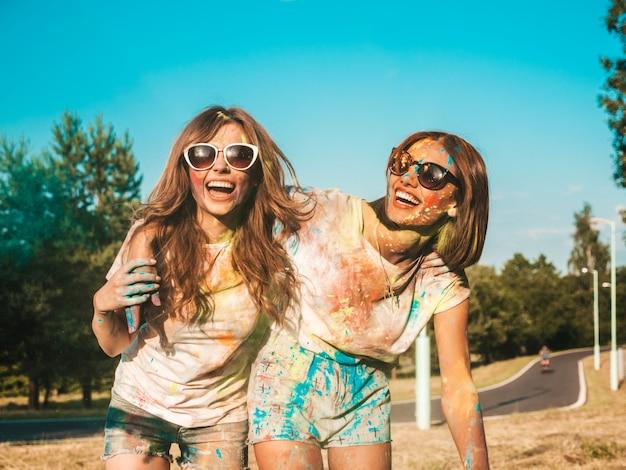 Dos chicas guapas felices haciendo fiesta en el festival de colores holi