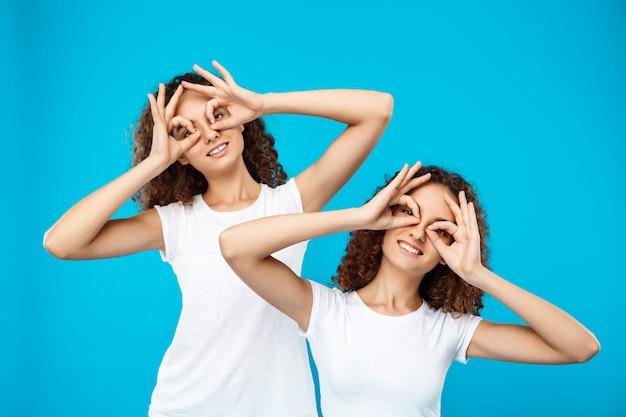 Dos chicas guapas gemelas sonriendo, bromeando sobre la pared azul