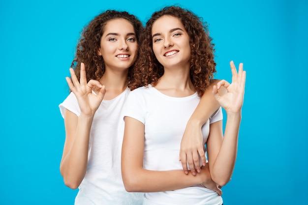 Dos chicas guapas gemelas sonriendo, mostrando bien sobre la pared azul