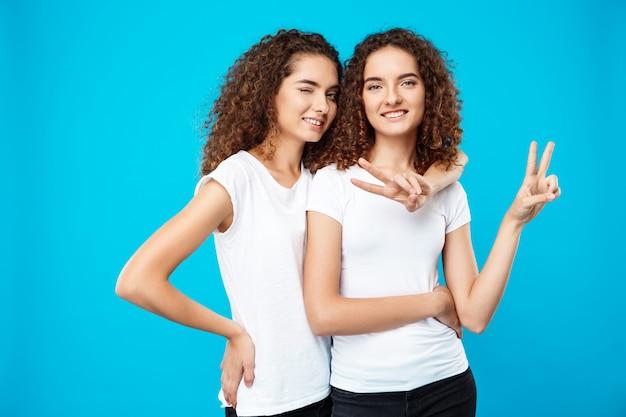 Dos chicas guapas gemelas sonriendo, mostrando paz sobre la pared azul