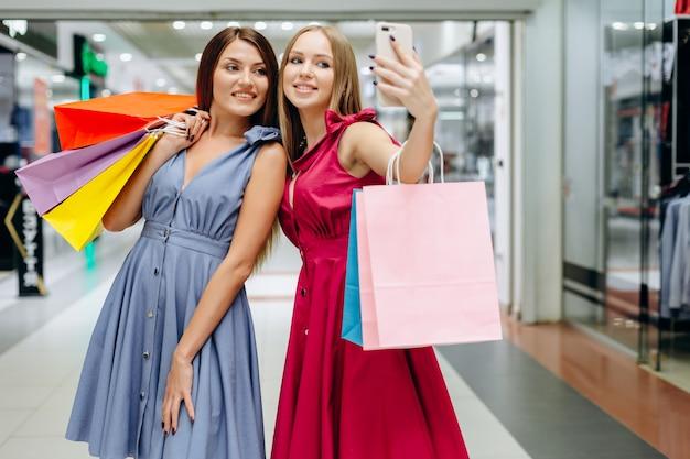 Dos chicas guapas se hacen selfies en el centro comercial después de ir de compras