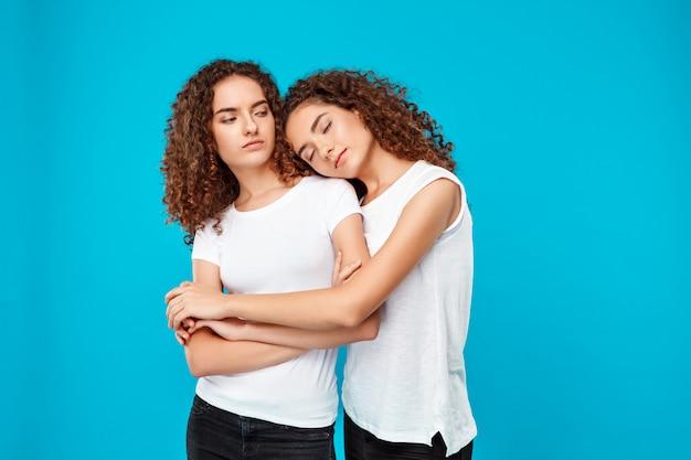 Dos chicas guapas jóvenes gemelas abrazándose, sonriendo sobre la pared azul