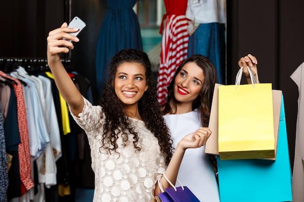 Dos chicas guapas jóvenes haciendo selfie en centro comercial.