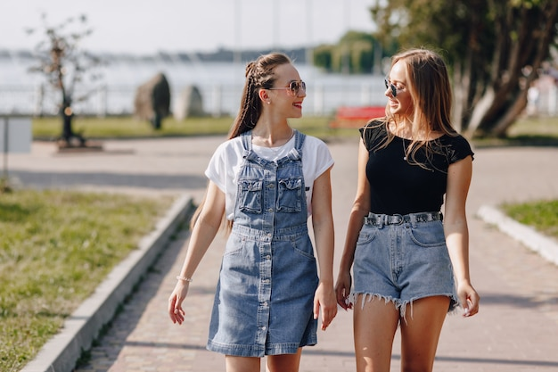 Dos chicas guapas jóvenes en un paseo por el parque. un día soleado de verano, alegría y amistades.