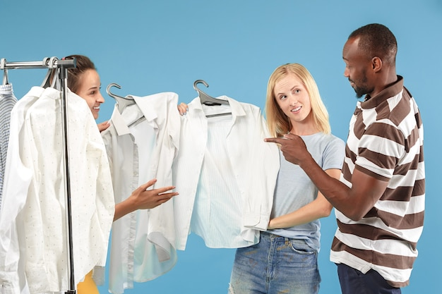 Las dos chicas guapas mirando vestidos y probándose mientras eligen en la tienda
