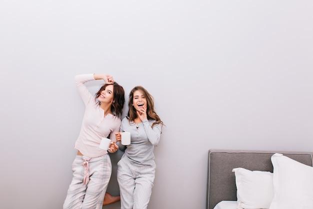 Dos chicas guapas en pijama de noche con tazas divirtiéndose en el dormitorio en la pared gris.