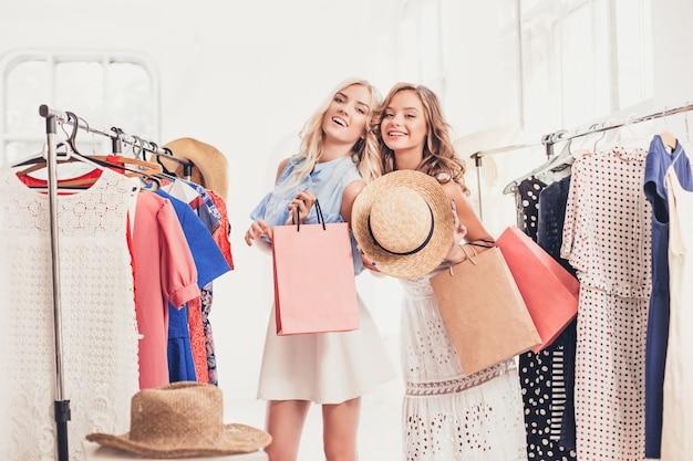 Dos chicas guapas que miran vestidos y se lo prueban mientras eligen en la tienda