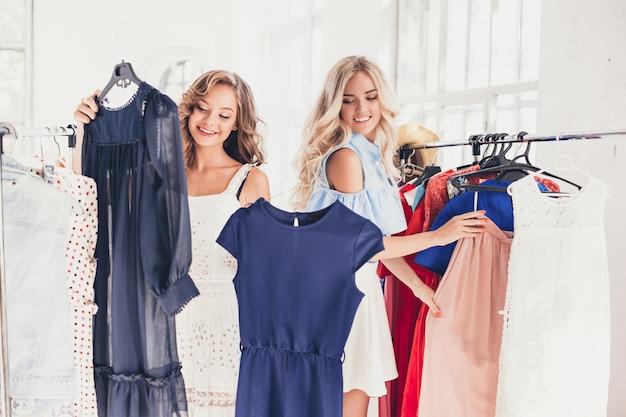 Las dos chicas guapas que miran vestidos y se lo prueban mientras eligen en la tienda