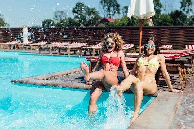 Dos chicas guapas que se relajan en la piscina. chicas rubias y asiáticas que se establecen en los sillones de la piscina. amigos divirtiéndose en verano. concepto de estilo de vida.