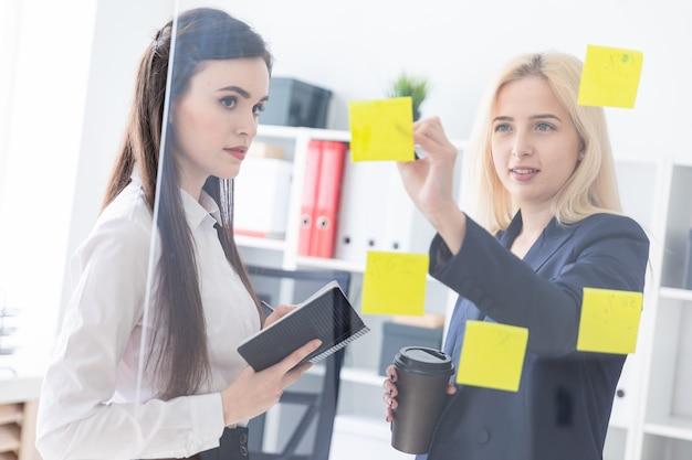 Dos chicas hablando en la oficina. las niñas son un diálogo cerca de un tablero transparente con pegatinas.