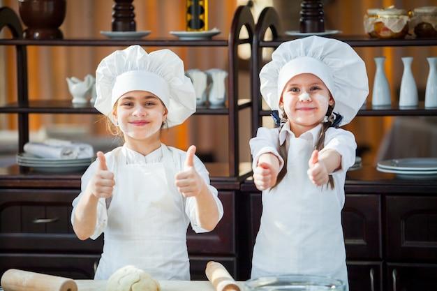 Dos chicas hacen masa de harina.