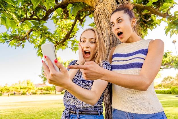 Dos chicas haciendo caras de sorpresa extendiendo la boca y los ojos apuntando y mirando smartphone pasando tiempo en la naturaleza del parque de la ciudad. mujeres jóvenes que se divierten con la red social debido a la tecnología móvil wi-fi