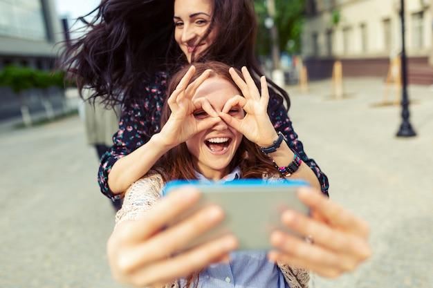 Dos chicas haciendo divertidas selfies en la calle, divirtiéndose juntas