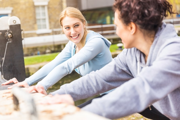 Dos chicas haciendo ejercicios de estiramiento al aire libre en londres