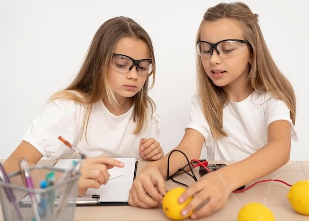 Dos chicas haciendo experimentos científicos con limones.
