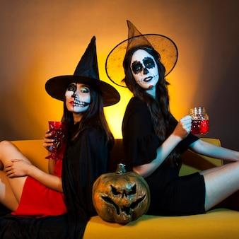 Dos chicas de halloween en sofá