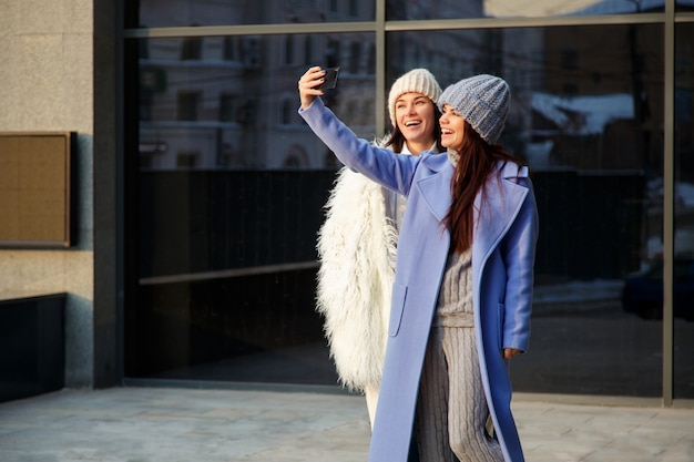 Dos chicas hermosas con gorras de lana que toman selfie usando un teléfono inteligente al aire libre en invierno