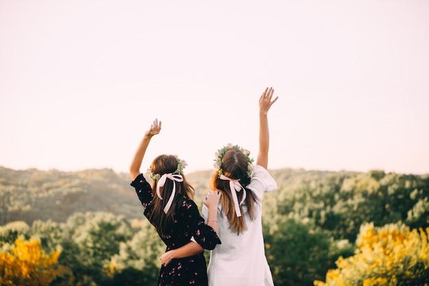 Dos chicas jóvenes se abrazan durante la puesta de sol en el campo con concepto de amistad de copas de vino