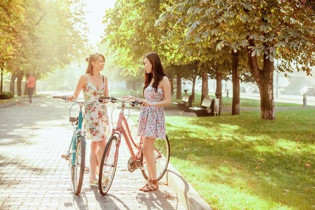 Las dos chicas jóvenes con bicicletas en el parque