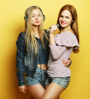 Dos chicas jóvenes cantando sobre fondo amarillo