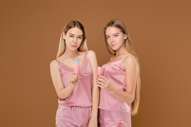 Dos chicas jóvenes con crema para el acné en las manos