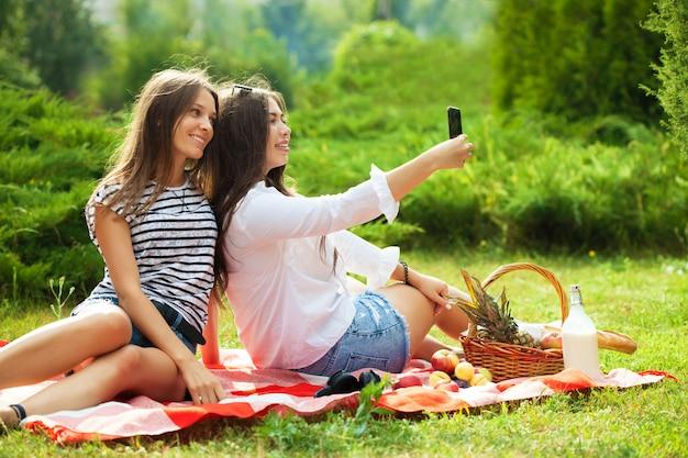 Dos chicas jóvenes divirtiéndose en el picnic, haciendo selfie en un teléfono inteligente