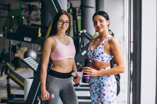 Dos chicas jóvenes entrenando en el gimnasio con equipo