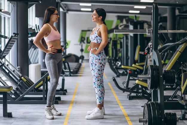 Dos chicas jóvenes entrenando juntas en el gimnasio