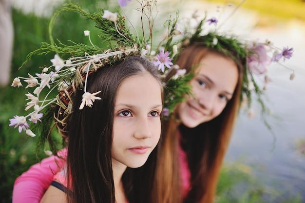 Dos chicas jóvenes en guirnaldas de flores silvestres