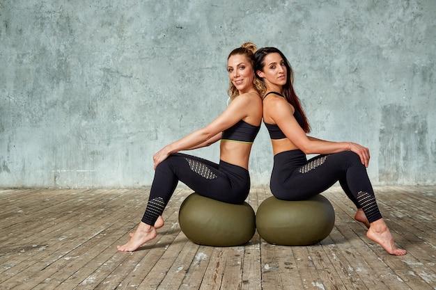 Dos chicas jóvenes y hermosas de fitness en el gimnasio posando con pelotas de fitness contra una pared gris
