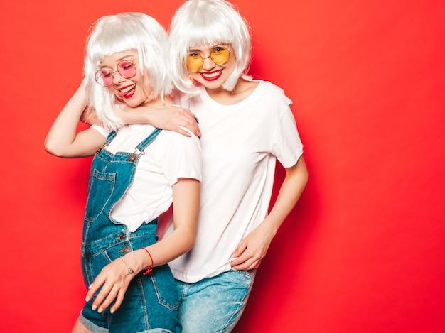 Dos chicas jóvenes hipster sexy con pelucas blancas y labios rojos. hermosas mujeres de moda en ropa de verano. modelos despreocupados posando junto a la pared roja en verano de estudio con gafas de sol