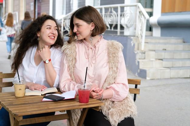 Dos chicas jóvenes que se sientan en una tabla en un café de la calle.
