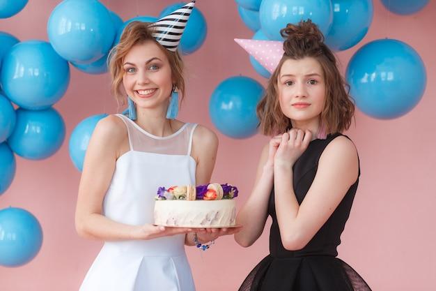 Dos chicas jóvenes que sostienen la torta de cumpleaños y muestran emociones muy emocionadas.